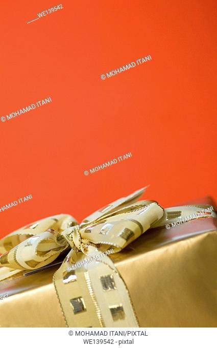 Vertical Shot of a golden gift box on a red background