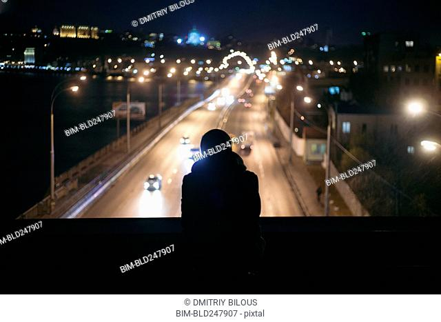 Silhouette of person watching traffic from overpass at night