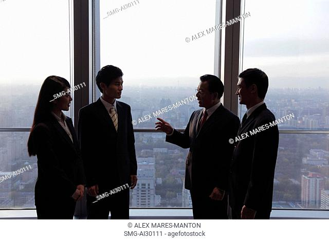 Four businesspeople talking in front of a window