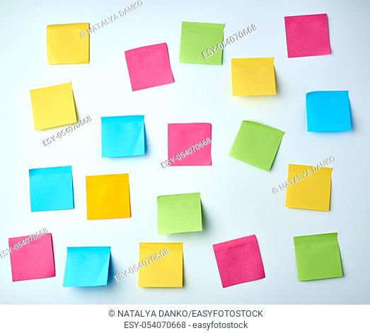 lot of blank square paper multicolored stickers on a white wall, close up