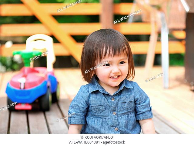 Mixed-race young girl playing on wooden deck