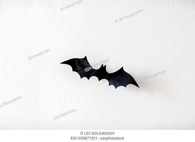 halloween, decoration and scary concept - black bat hanging on strings over white background
