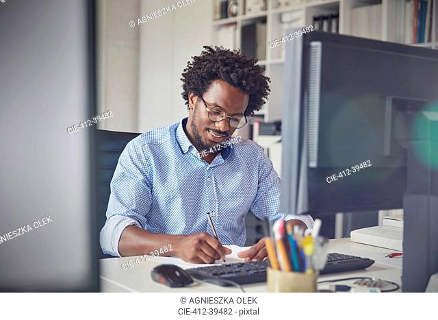 Businessman taking notes at computer in office
