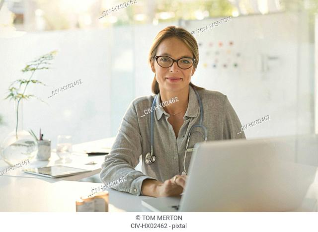 Portrait confident female doctor working at laptop in doctor's office