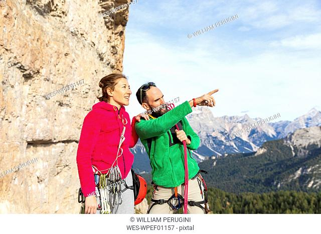 Italy, Cortina d'Ampezzo, couple with climbing equipment looking at view an talking in the Dolomites mountains
