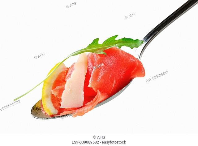 Thin slices of raw beef on spoon