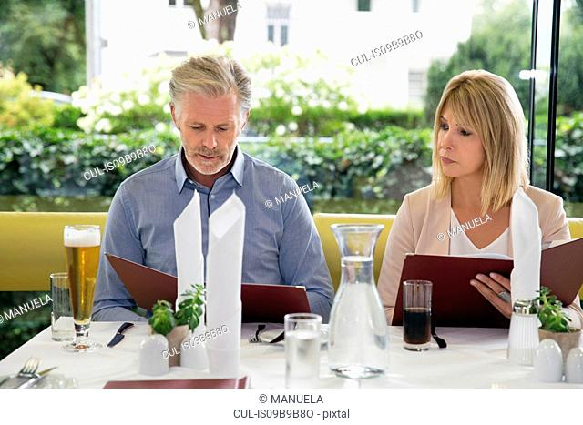 Couple al fresco dining at restaurant, selecting from menu