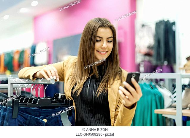 Young woman reading a text message in shopping mall Debica, Poland