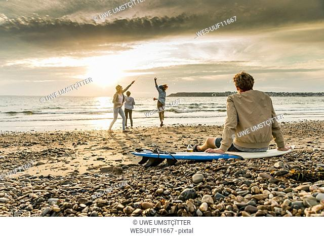 Young man on surfboard watching friends making soap bubbles on the beach at sunset