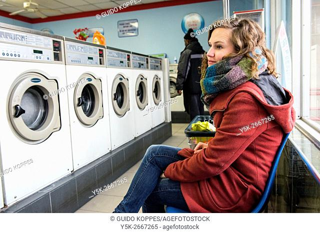New York City, USA. Young brunette woman waiting for her laundru to finish inside a Chinese run laundrette