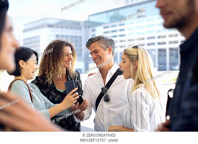 Group of happy casual businesspeople sharing cell phone on urban square