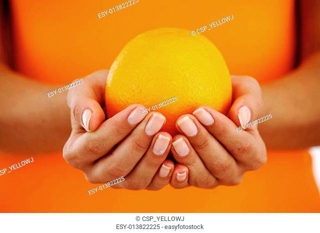 orange in woman hands