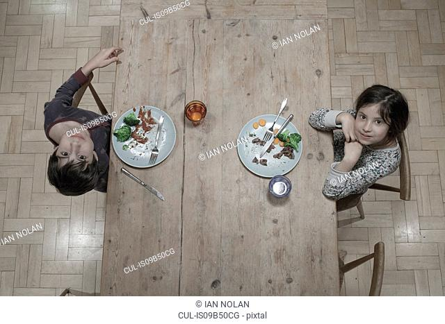 Overhead portrait of sister and brother eating dinner at kitchen table