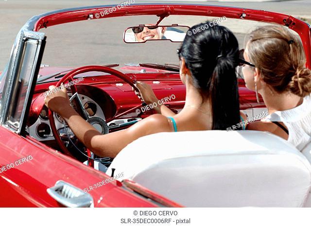 Women driving vintage convertible