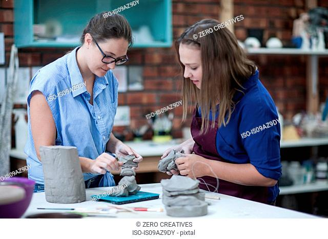 Two female potters shaping clay on workbench in workshop