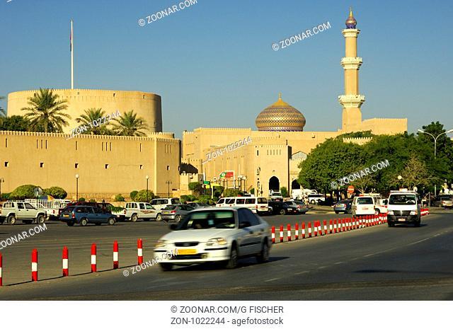 Strassenverkehr am Hauptplatz vor der Festung und der Grossen Moschee, Nizwa, Sultanat Oman / Road traffic passing by the main square in front of the Fort of...