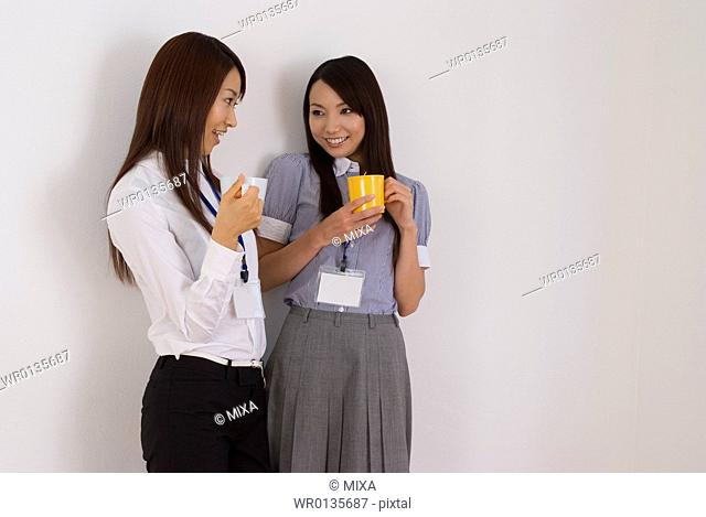 Two young women talking with cup of coffee