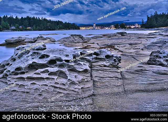 sandstone formations and view of downtown at dusk from Newcastle Island Provincial Marine Park, Nanaimo, British Columbia, Canada
