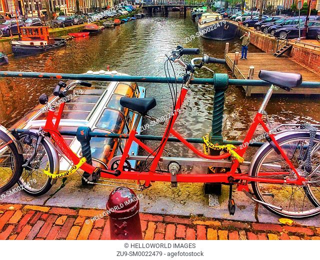 Tandem bicycle chained to railings above canal, Amsterdam, Netherlands