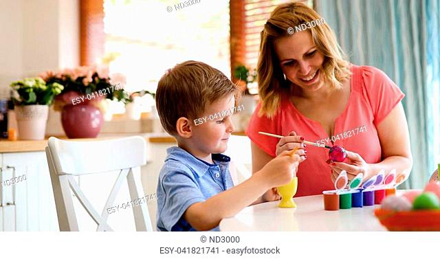 Young mother and her cute son having fun while painting eggs for Easter