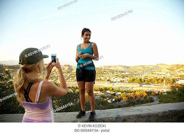 Woman photographing friend