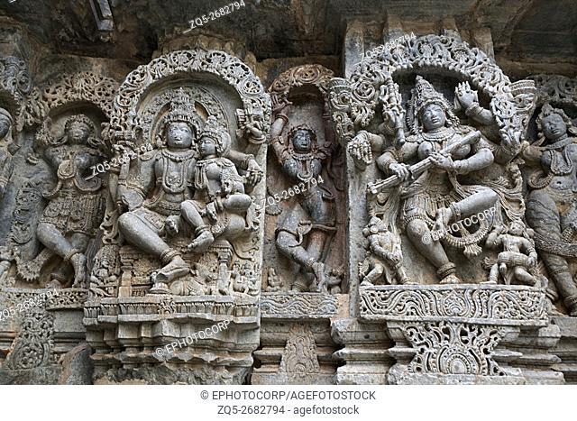 Ornate wall panel reliefs depicting (from left) Shiva-Parvati and dancing Sarswati, Kedareshwara temple, Halebidu, Karnataka, india