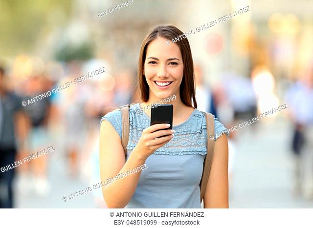 Happy woman holding a smart phone and looking at camera on the street