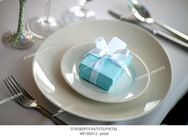 Festive table setting with handmade gift box on plate. Light blue handmade gift box in plate and fork on wedding table
