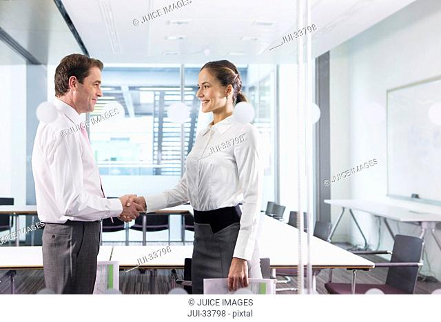 Businessman and businesswoman shaking hands in conference room