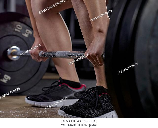 Close-up of young woman doing weightlifting with barbell