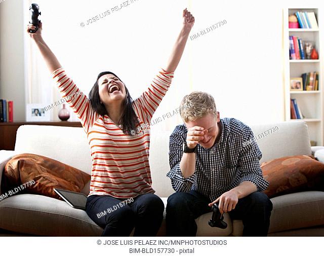 Cheering girlfriend defeating boyfriend at video games on sofa