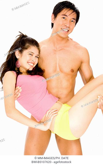 muscular asiatic man carrying young woman in underwear