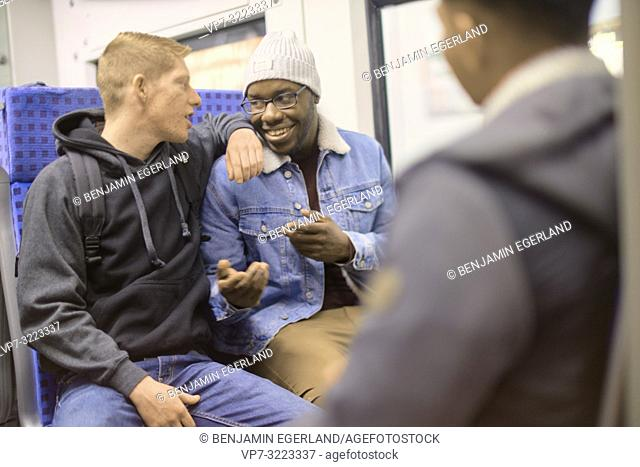 young men talking in public transport, in Munich, Germany