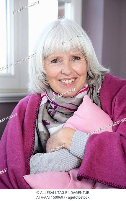 Elderly lady sitting on a couch with a woollen blanket