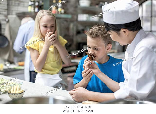 Boy and girl smelling food from female chef in cooking class