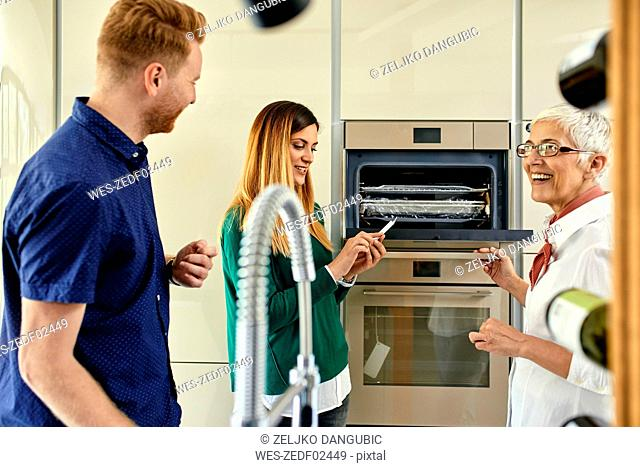 Shop assistant explaining oven to couple shopping for a new kitchen in showroom