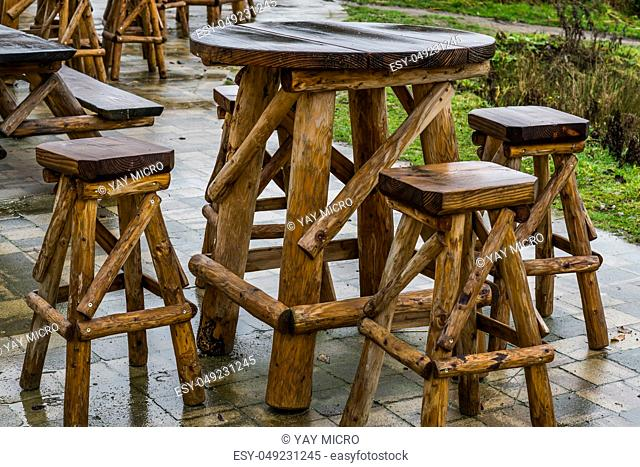 empty wooden table with bar crutches, garden or terrace furniture, rainy day in the catering industry