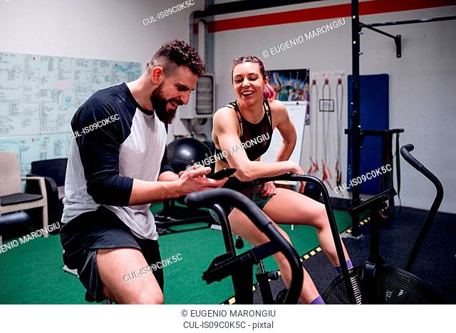 Young woman and man training together on gym exercise bikes, looking at smartphone