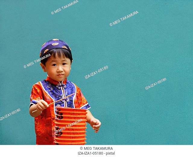Portrait of a boy holding a Chinese lantern