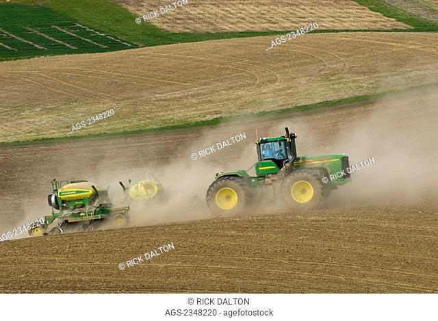 Agriculture - A John Deere tractor and air seeder planting garbanzo beans (chick peas) in the rolling hills of the Palouse Region / near Pullman, Washington