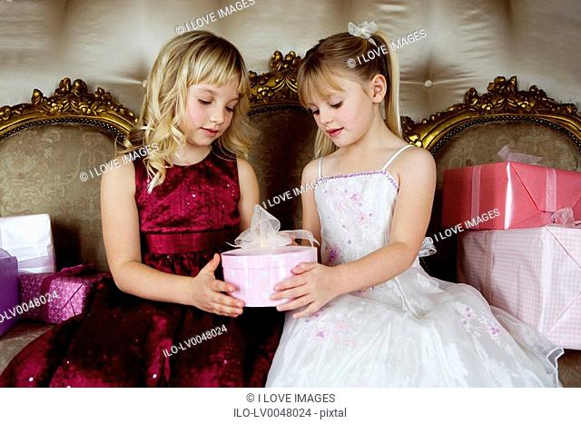 Little girls sharing birthday presents