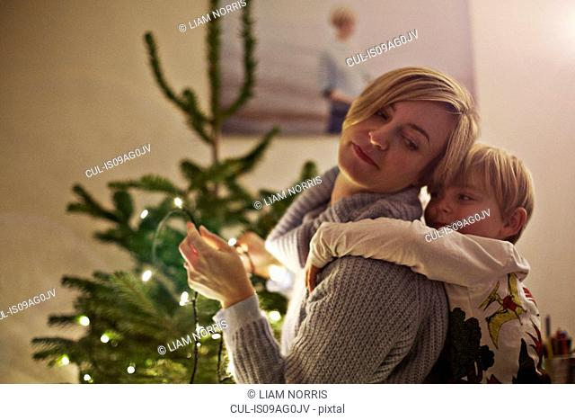 Mother and son hugging next to christmas tree