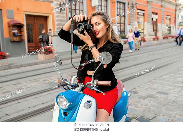 Portrait of young woman on scooter taking photograph on cobbled street, Odessa, Ukraine