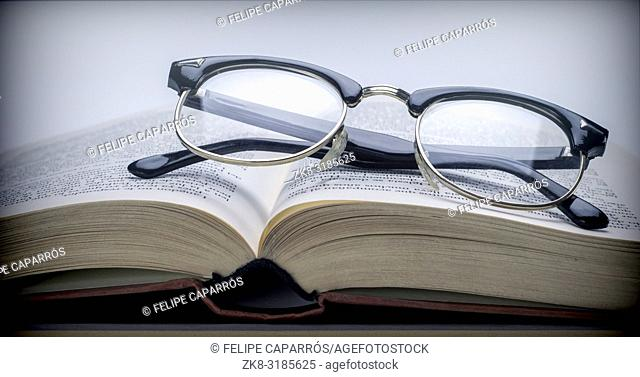 Glasses vintage on a book isolated on white background