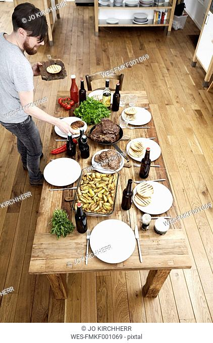Man serving dish on wooden table