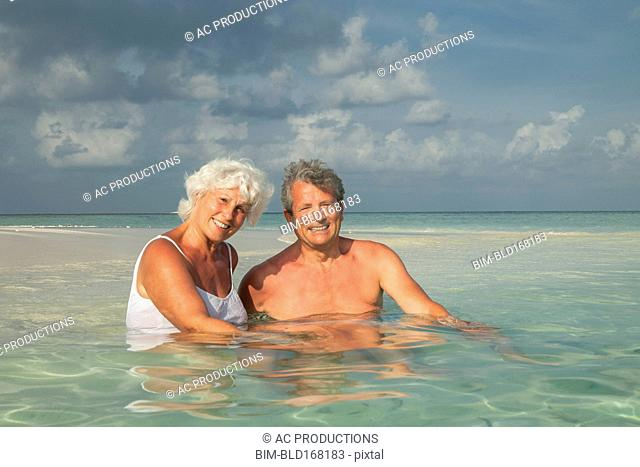 Older Caucasian couple swimming on beach