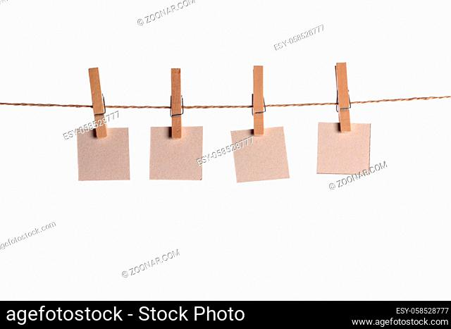Four paper blank notes hanging on the rope isolated on white background