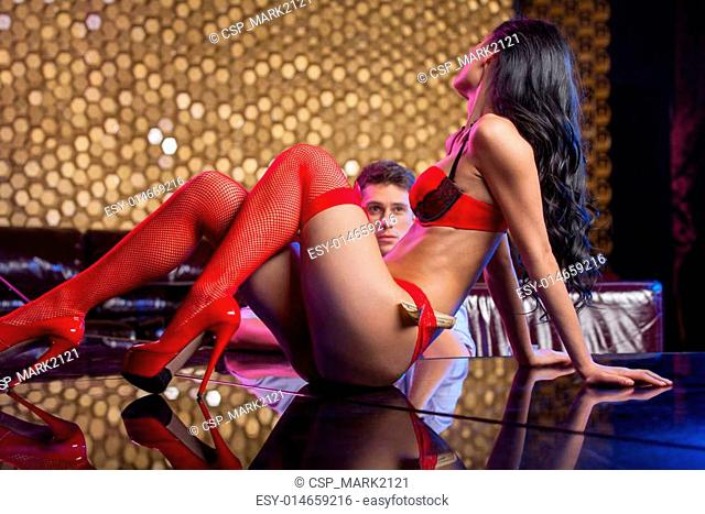 Sexy striptease dancer dancing in front of man in red lingerie and hose. Man watching seductive strip dance