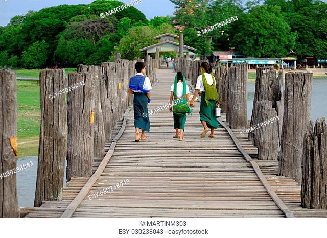 Amarapura, Myanmar - 28 June, 2015: Children in colorful clothes walk to school on U Bein bridge in Amarapura, Myanmar