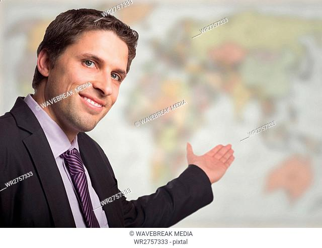 Business man gesturing towards blurry map